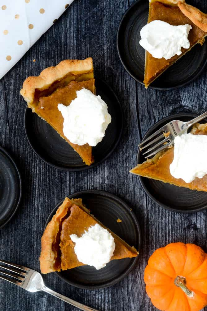 aerial view of 4 plates with pumpkin pie with whipped cream against black background.