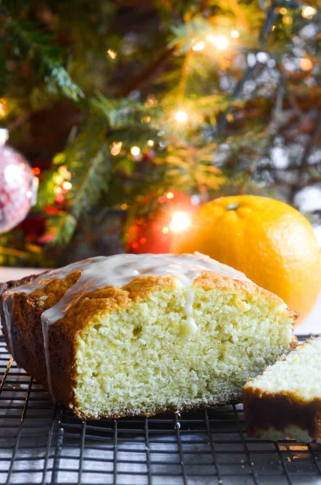 orange pound cake with slice cut into in front of Christmas tree with lights twinkling.