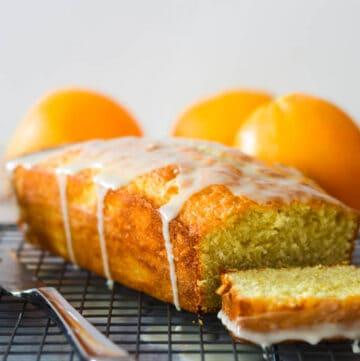 orange pound cake with first slice cut on wire rack