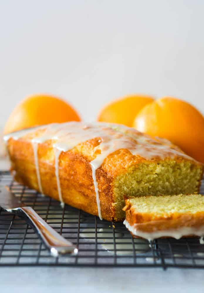 side view of pound cake with orange glaze drizzled on top and oranges in the background.