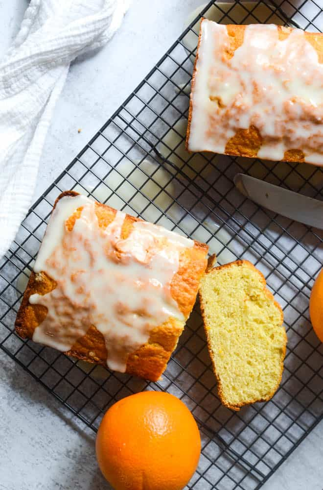 Flat lay of two loaves of orange pound cake on wire rack with one slice cut into and oranges scattered around.