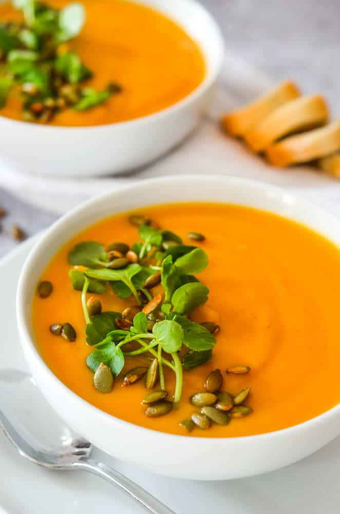 close up picture of a bowl of butternut squash soup with watercress and pepitas.