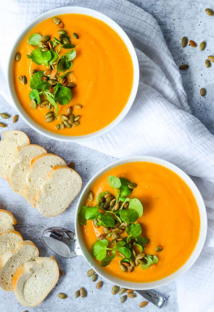 flat lay picture of two large bowls of butternut squash soup in white bowls with slices of baguette strewn around.