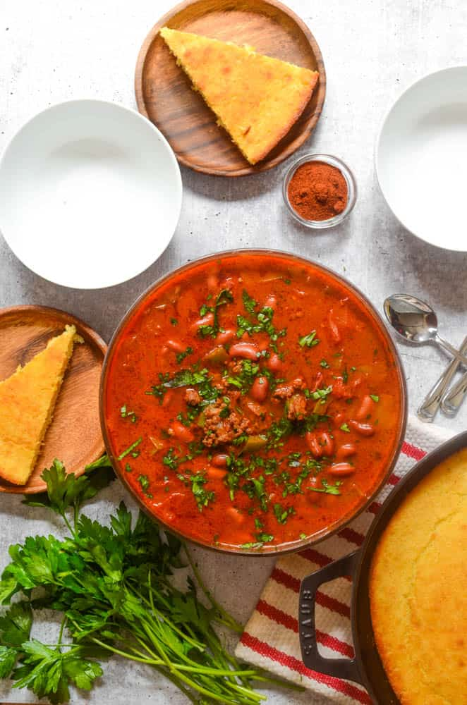 aerial view of large bowl of chili with smaller plates of cornbread next to the bowl.