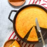 aerial picture of cornbread in cast iron skillet with two pieces cut out.