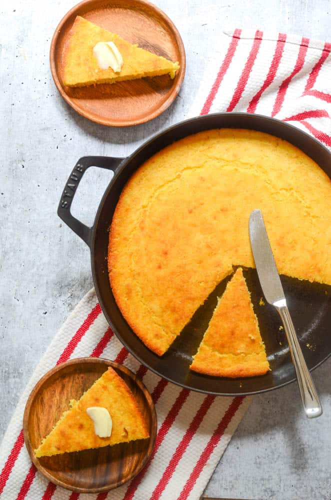 flat lay picture of cast iron cornbread with a couple of slices cut out and knife resting on top of cornbread.