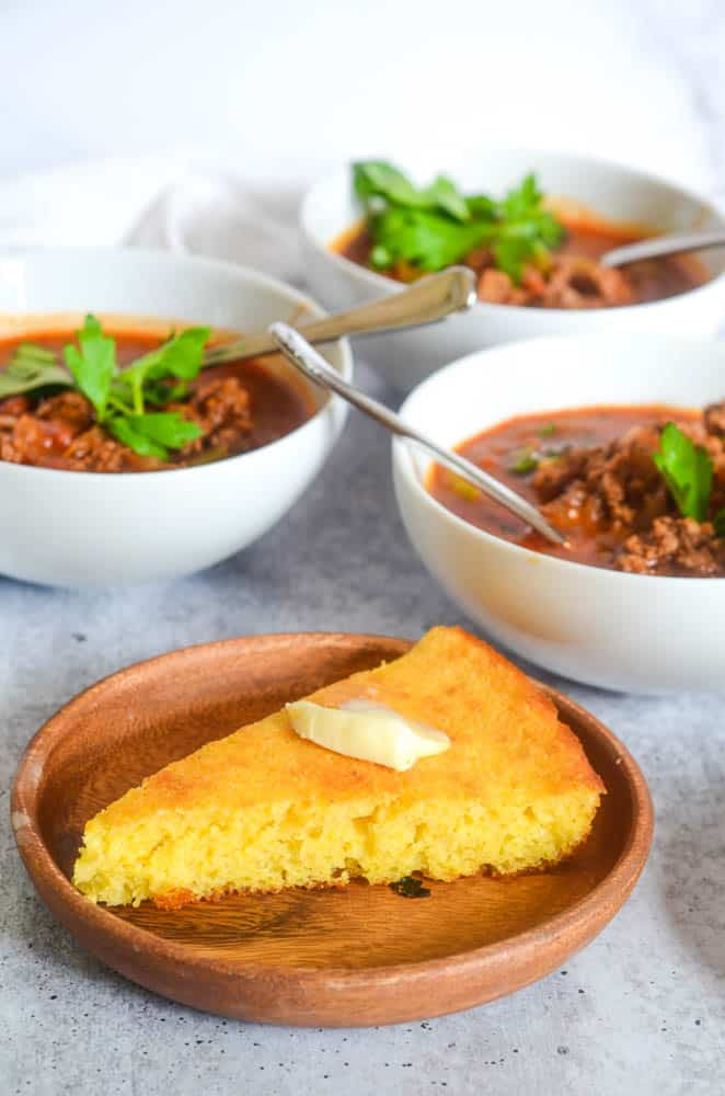 side view of one piece of cornbread with slab of butter on top and bowls of chili in the background.