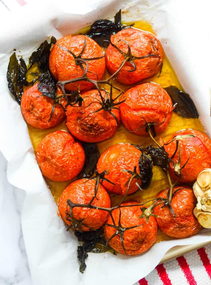 aerial picture of a tray of roasted tomatoes with head of garlic and basil scattered.