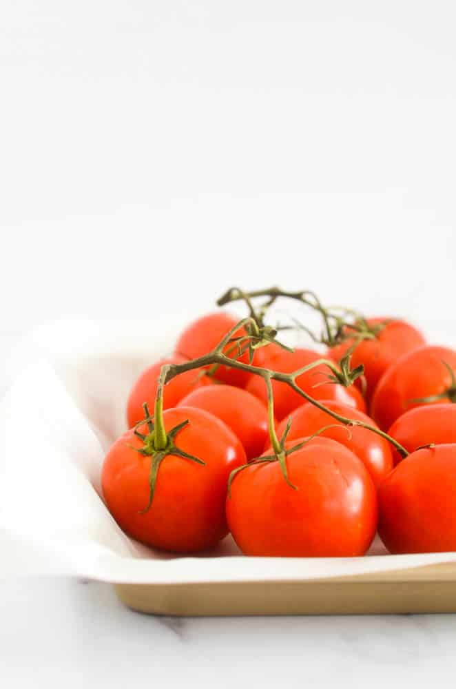 side view of vine-ripe tomatoes on rimmed baking tray with parchment paper ready to be roasted.