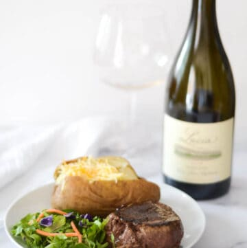 side photo of a plate with filet, baked potato, and salad on it and wine bottle and glass behind plate.