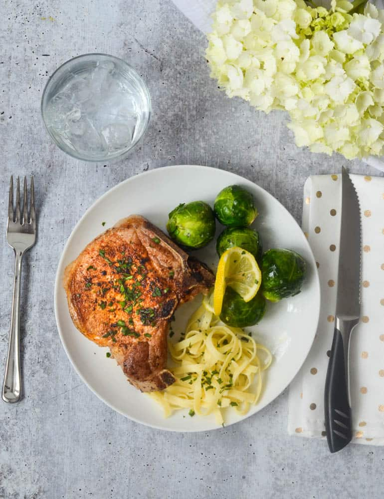 aerial shot of white dinner plate with bone-in pork chop, fettuccine, and brussels sprouts.