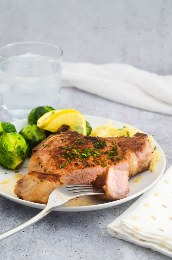 close up picture of pork chop with a bite of meat on a fork.