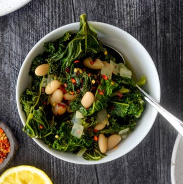 aerial photo of white bowl of braised kale with lemon half.