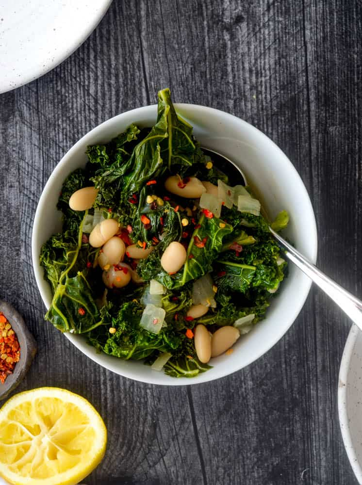 aerial picture of white bowl of braised kale with a spoon in it.