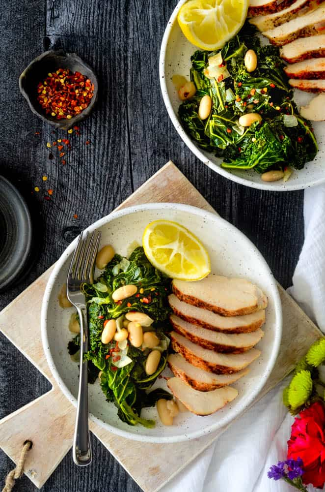 flat lay photo of two plates of roasted chicken and braised kale on a white plate with lemon wedge. red pepper is in a pinch pot against black background.