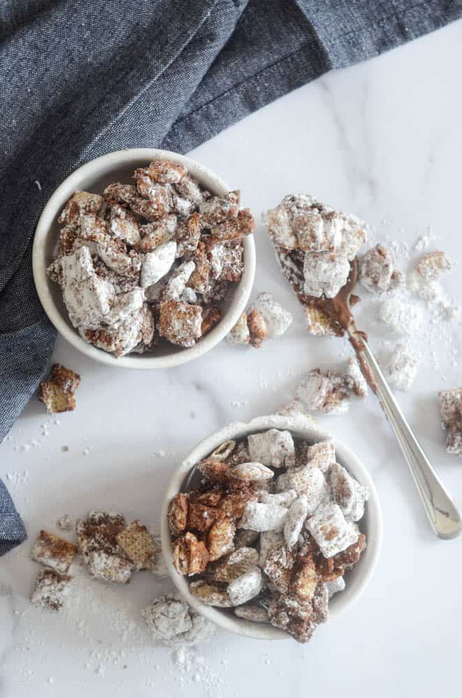 aerial view of two white bowls of puppy chow with messy spoon on marble backdrop.