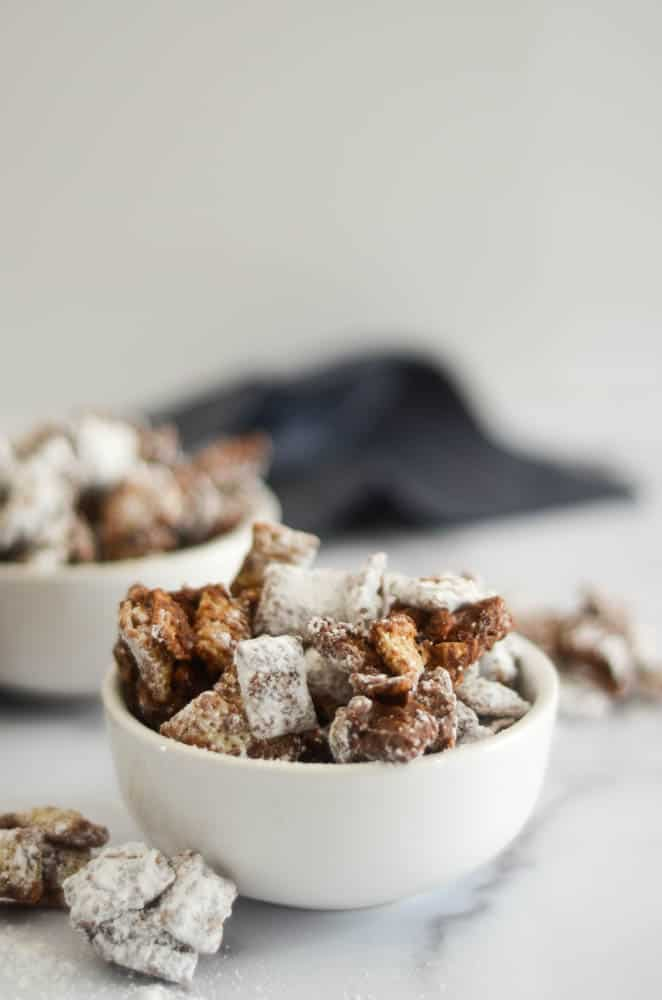 up close picture of one white bowl of puppy chow with another bowl and blue napkin in the background.