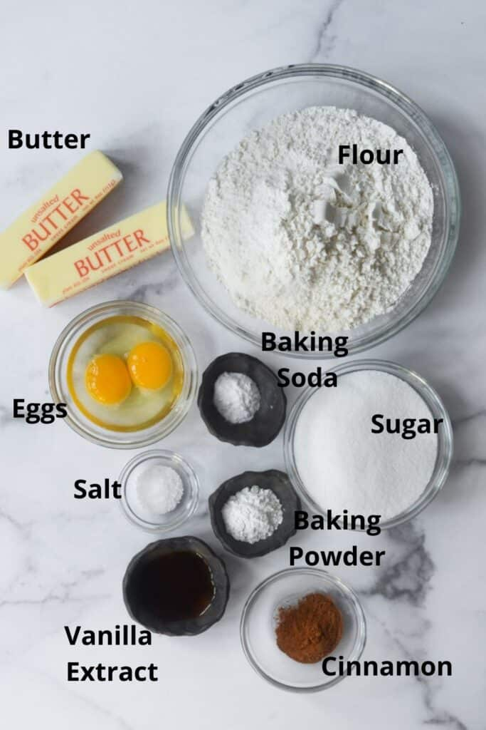 all of the ingredients needed with text labels: flour, baking soda, baking powder, sugar, cinnamon, vanilla extract, salt, eggs, and butter.