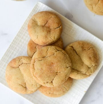stack of snickerdoodle cookies on white square plate.