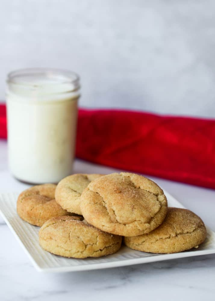 side picture of a plate of snickerdoodles with a glass of milk in the background with a red napkin.
