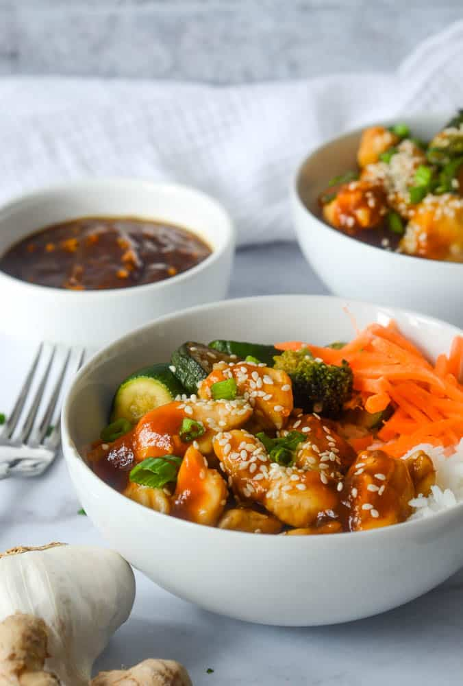 side picture of a teriyaki chicken bowl topped with sesame seeds.