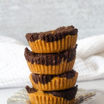 stack of 4 almond butter cups with white cloth in background.