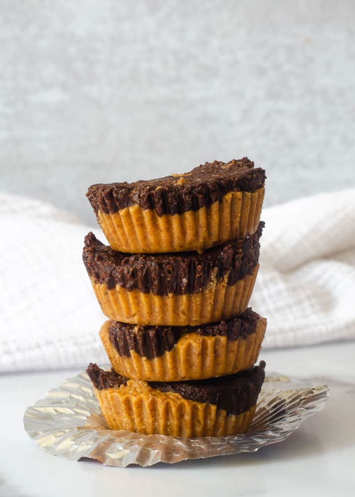 4 almond butter cups stacked on a muffin liner with white napkin in background.
