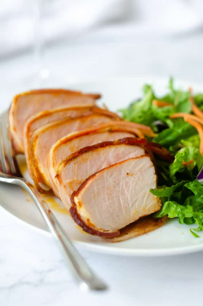 slices of pork chop in neat row on a white plate with fork next to slices.