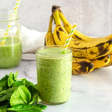 banana spinach smoothie in mason jar with loose spinach and bananas in background.