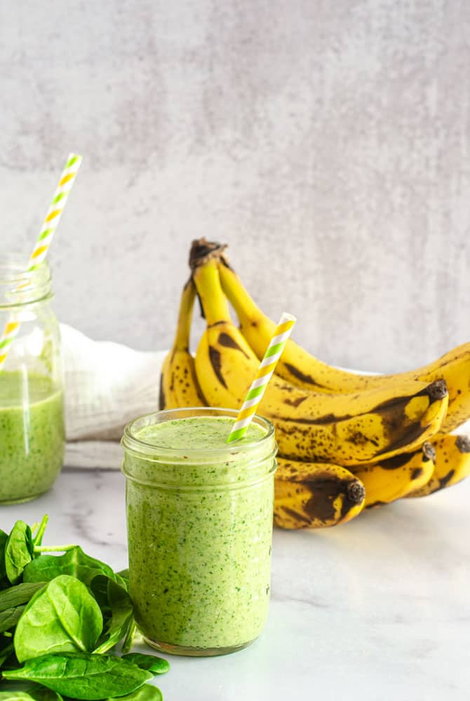 green smoothie on marbled counter with ripe bananas in the background.