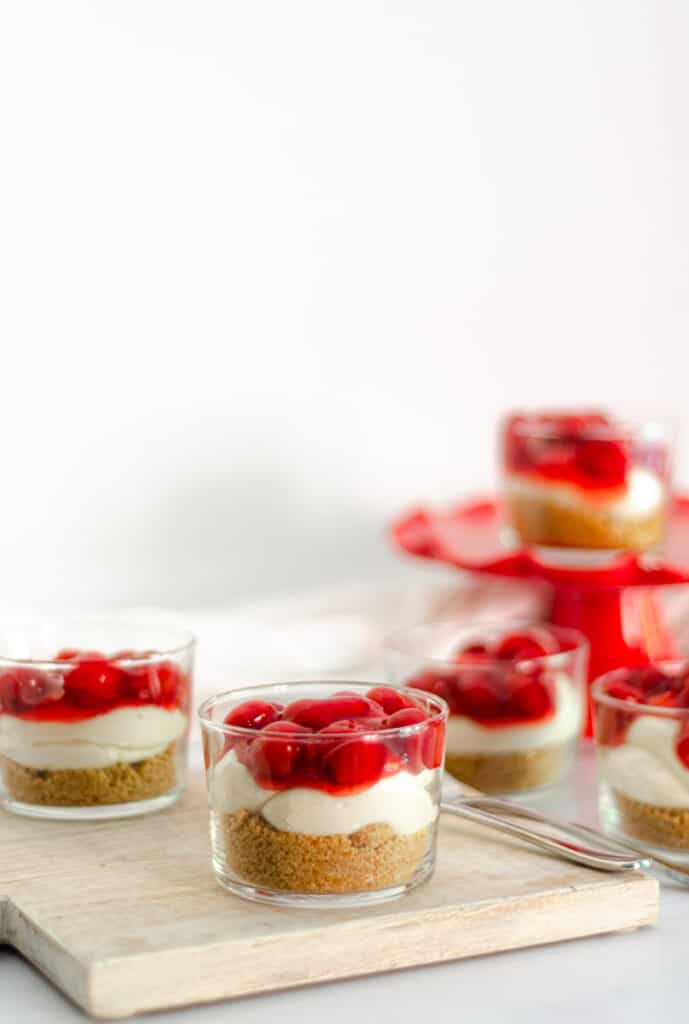 cheery cheesecake parfait in clear glass on wooden board with other parfaits in the background.
